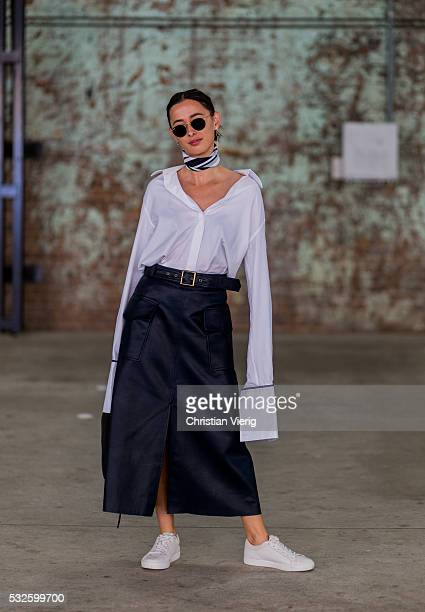 Eleanor Pendleton a white oversized Anna Quan button shirt with long sleeves and black leather pants and white sneaker at MercedesBenz Fashion Week...