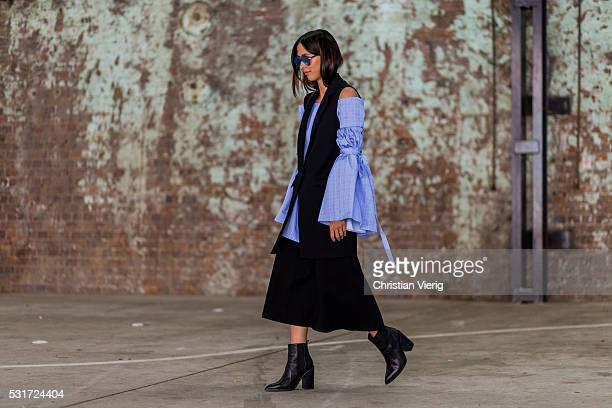 Eleanor Pendleton wearing an off shoulder oversized blue top from Ellery a black Hansen Gretel Elodie vest and Pipper skirt outside Yeojin Bae at...