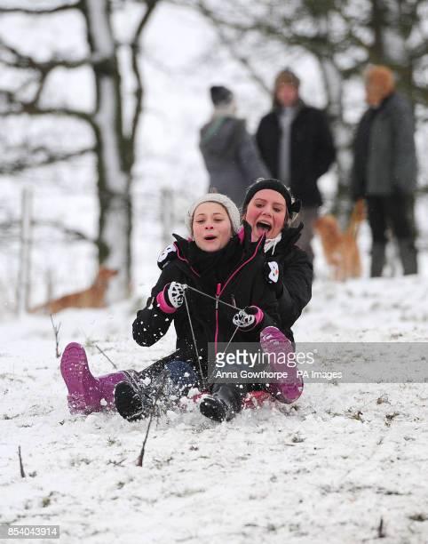 Eleanor Penfold and Chloe Jones sledge down Chapel Hill in Pocklington East Yorkshire after overnight snowfall