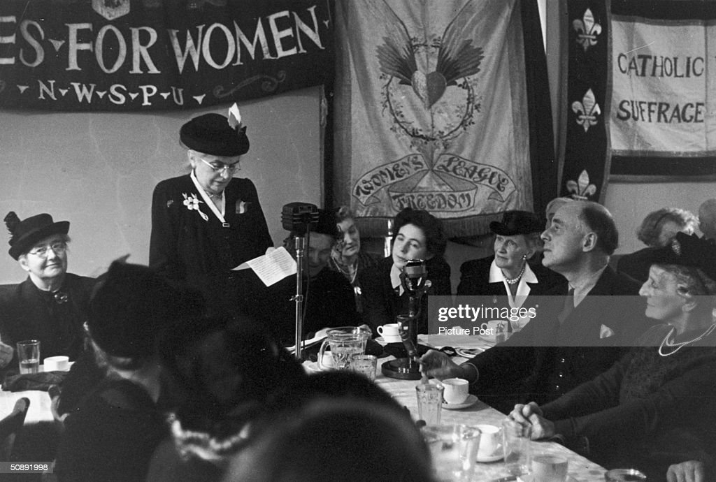 Eleanor Rathbone (1872 - 1946), a former campaigner for women's suffrage, celebrates the Silver Jubilee of the Women's Vote in London, 20th February 1943. Banners for the NWSPU (National Women's Social and Political Union) and Women's Freedom League adorn the wall behind her. Original Publication - Picture Post - 1378 - Suffragettes: 25 Years After - pub. 1943.
