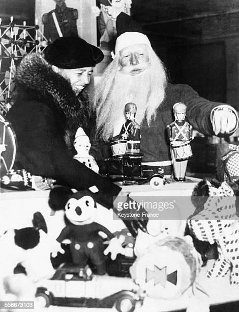 Eleanor Roosevelt First Lady et femme de Franklin Roosevelt et un homme déguisé en Père Noël dans un magasin de jouets le 22 décembre 1934 aux...