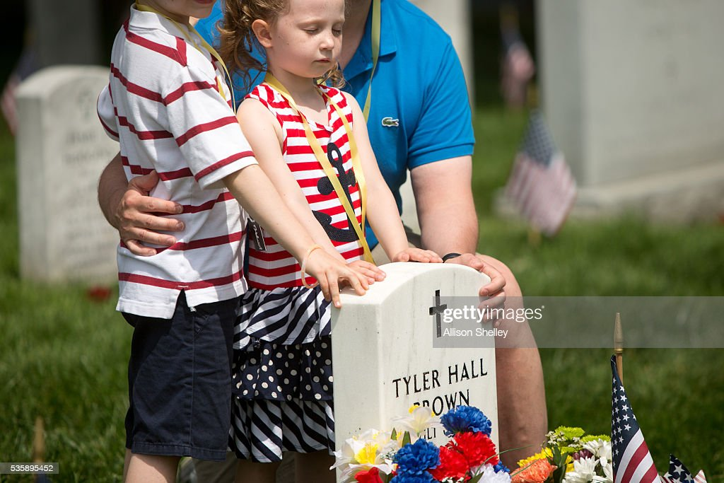 Eleanor Sitkiewicz, 4, of Richmond, Virginia, stands with her brother Henry, 7, and father Greg at the grave of Tyler Hall Brown, a college friend of her father, in Section 60, the burial ground for military personnel killed since 2001, at Arlington National Cemetery on May 30, 2016 in Arlington, Virginia. Brown was killed in Iraq in 2004 and Greg has been bringing his wife Sara and later the whole family to the grave site since then. 'There is nothing else we have done that consistently for so long,' says Sara. 'Tyler has changed the meaning of Memorial Day for us.'