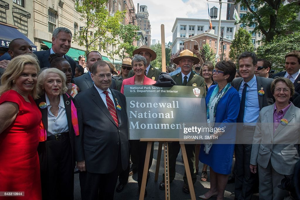 Elected officials, advocates and New Yorkers including from left, Congresswoman Carolyn Maloney, LGBT activist Edith Windsor, Mayor Bill de Blasio, Congressman Jerrold Nadler, Secretary of the Interior Sally Jewel, US National Park Service Director Jonathan Jarvis, Valerie Jarrett, NY State Senator Brad Holman and NY State Assembly member Debra Glick unveil the sign designating Stonewall Inn a National Monument,on June 27, 2016 in New York. / AFP / Bryan R. Smith