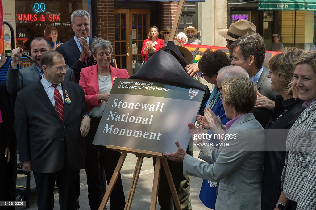 Elected officials, advocates and New Yorkers including from left, US Assemblymember Jerrold Nadler, Mayor Bill de Blasio, Secretary of the Interior Sally Jewel, Valerie Jarrett and NY State Assemblymember Debra Glick unveil the the sign design designating Stonewall Inn a National Monument, on June 27, 2016 in New York. / AFP / Bryan R. Smith