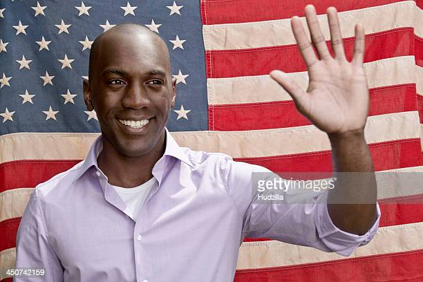 Elected politician waving in front of American flag