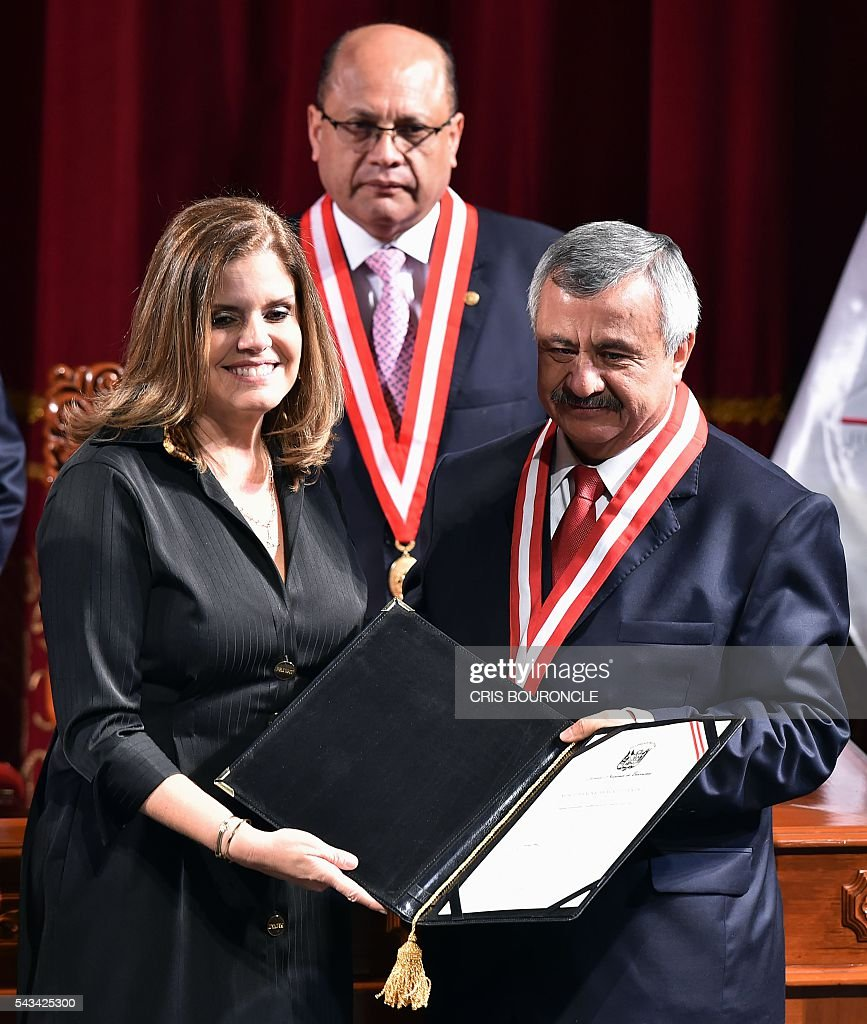 Elected second Vice-President Mercedes Araoz (L) receives her credentials from the president of the National Electoral Jury (JNE), Francisco Tavara, during a ceremony in Lima on June 28, 2016 a month before taking office. Peruvian President-elect Pedro Pablo Kuczynski, his Vice-President Martin Vizcarra and Araoz will be sworn in for a five-year term on July 28. / AFP / CRIS