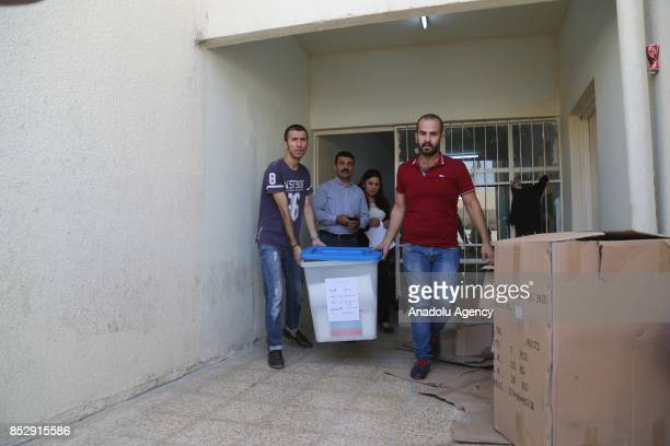 Election committee workers carry ballot boxes to the Barzani Namir high school polling station ahead of the upcoming Kurdish Regional Government...