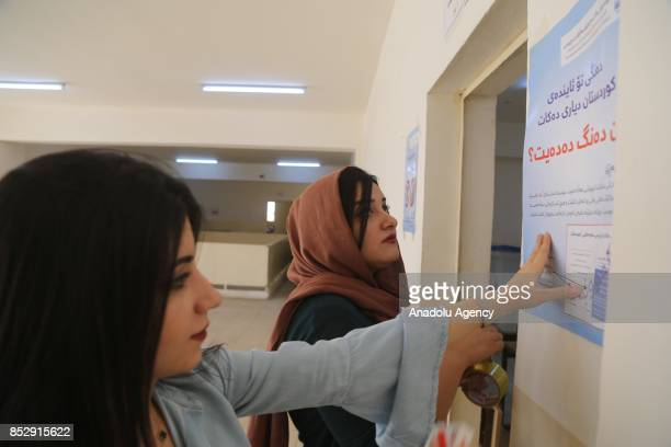 Election committee workers put directions to cast vote at the Barzani Namir high school polling station ahead of the upcoming Kurdish Regional...