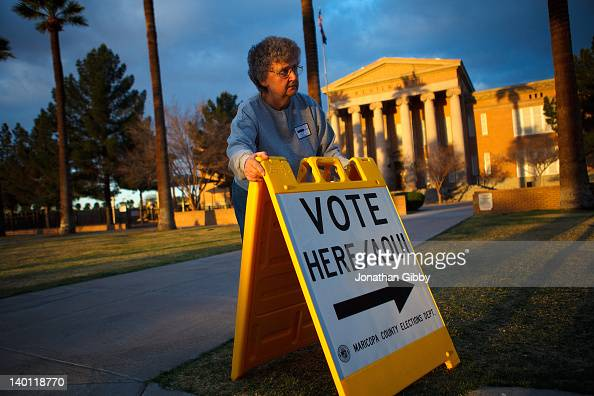 Election day volunteer Vicki Groff places a sign to direct voters to a polling station at Kenilworth School February 28 2012 in Phoenix Arizona...