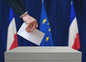 Election in France. Voter holds envelope in hand above vote ballot. French and European Union flags in background.