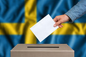 Election in Sweden. The hand of woman putting her vote in the ballot box. Swedish flag on background.