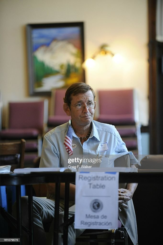 election judge mark trast sits at the registration table for precinct 521 outside the Barth hotel in denver