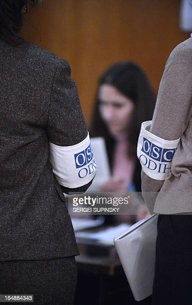 Election observers of the Organization for Security and Cooperation in Europe stand as electoral commission members count ballots at polling station...