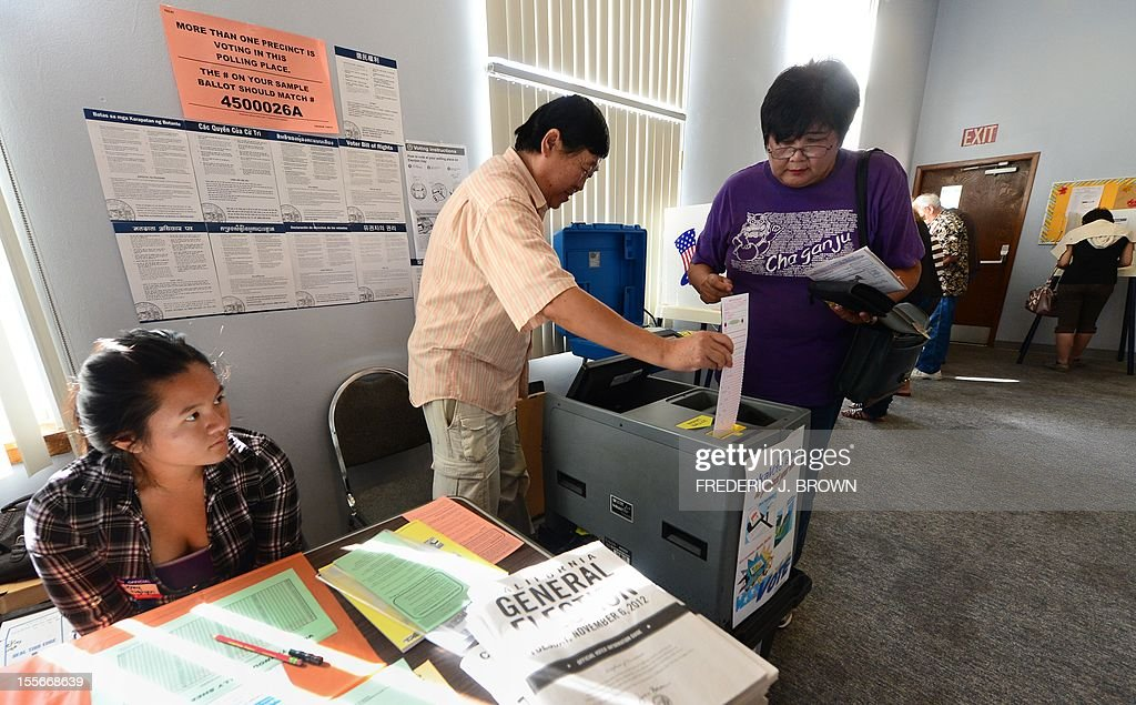 Election official Henry Tung (C) helps Kiyoko Nishi (R) drop her vote into the ballot box at a polling station at St. Paul's Lutheran Church in Monterey Park, Los Angeles County, on November 6, 2012 in California, as Americans flock to the polls nationwide to decide between President Barack Obama, his Rebuplican challenger Mitt Romney, and a wide range of other issues. Monterey Park is one of six cities in California's 49th Assembly District, the state's first legislative district where Asian-Americans make up the majority of the population. AFP PHOTO/Frederic J. BROWN