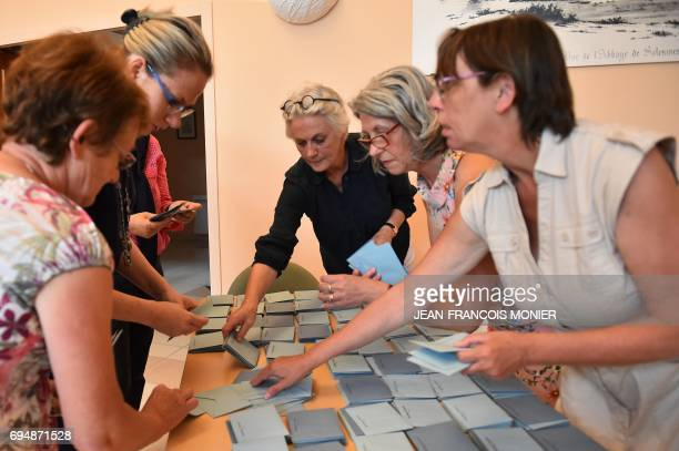 Election officials and former prime minister wife Penelope Fillon empty a ballot box to start counting votes at a polling station during the first...