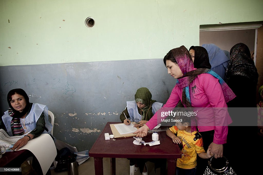 Election officials check the voter identification cards of Afghan women at a polling station for the parliamentary elections on September 18 2010 in...