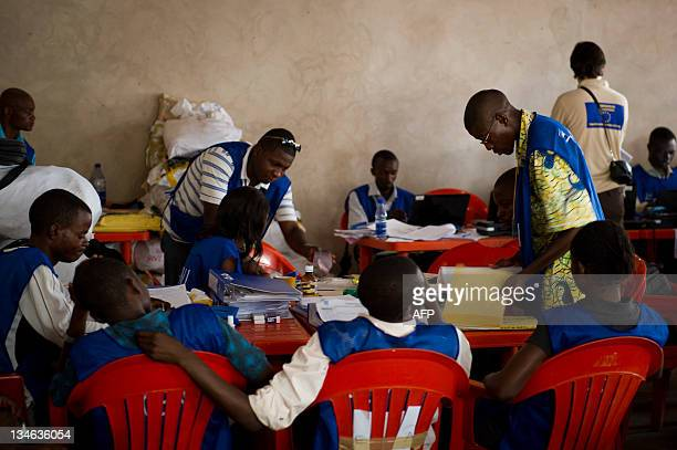 Election officials compile on December 3 2011 results from the November 28 elections as a European Union election observer circulates at the National...