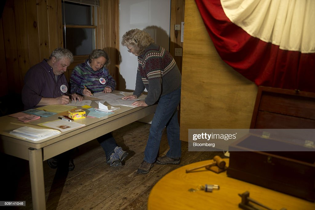 Election officials Les Schoof, left, and Nancy Ritger, center, certify votes at the town hall polling site during the New Hampshire presidential primary election in Harts Location, New Hampshire, U.S., on Tuesday, Feb. 9, 2016. According to the New Hampshire Secretary of State's office, the state has 383,834 voters who haven't declared a party affiliation, compared to 260,896 registered Republicans and 229,202 Democrats. Photographer: Andrew Harrer/Bloomberg via Getty Images