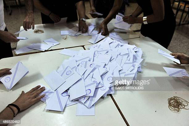 Election officials sort through a ballot box to count votes at a polling station in Thessaloniki on September 20 2015 Former Greek leftwing leader...