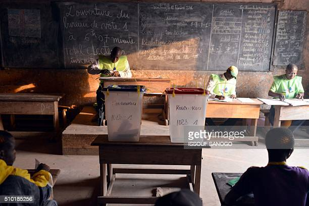 Election officials wait for voters at a polling station in Bangui on February 14 as people go to the polls to take part in the country's delayed...