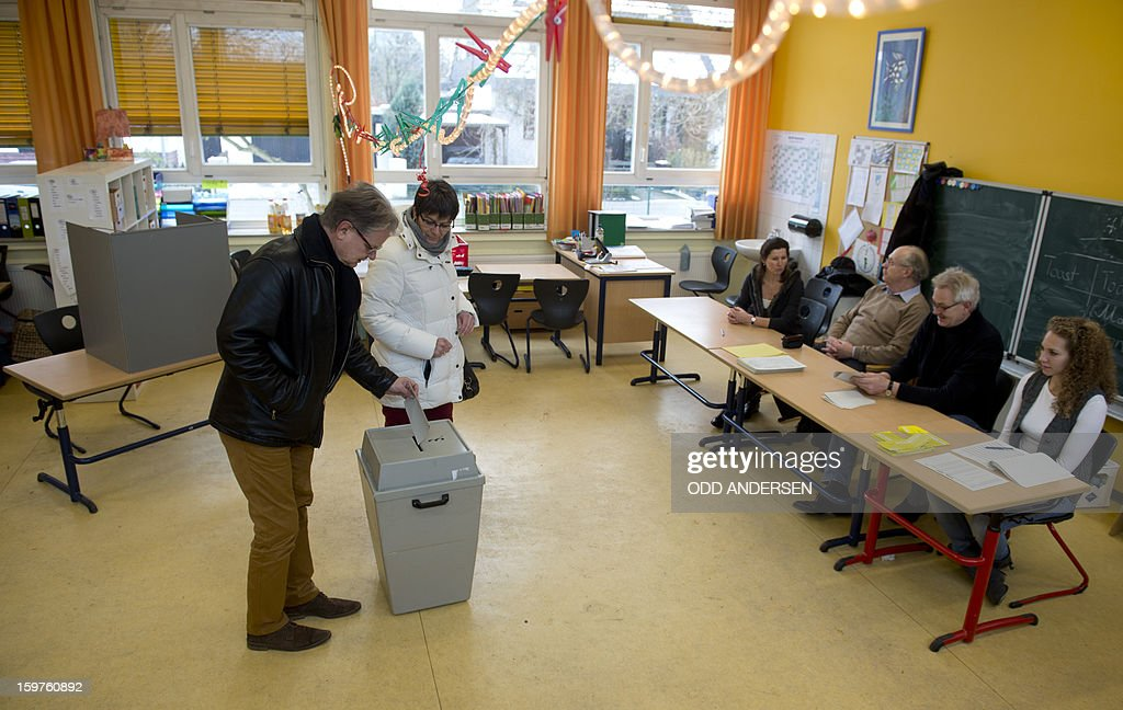 Election officials watch two voters as they cast their ballots at a polling station at the Friedrich-Dierks Schule in Isernhagen, Germany on January 20, 2013 on polling day of the local elections in the central German state of Lower Saxony.