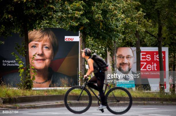 Election posters of German Chancellor Angela Merkel and her main rival Martin Schulz are seen as a cyclist cross Yorckstrasse in the Schoeneberg...