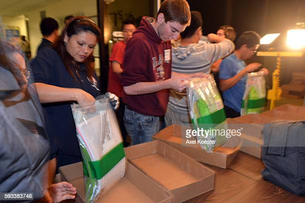 Election volunteers help gather and sort bags of ballots as they are driven in by Los Angeles Sheriff's deputies for recording and tallying at the LA...