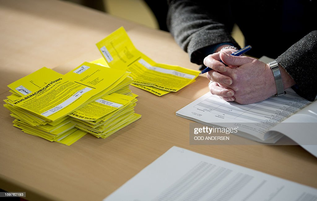 Election voting cards and the hands of an election official are pictured at a polling station at the Friedrich-Dierks Schule in Isernhagen, Germany on January 20, 2013 on polling day of the local elections in the central German state of Lower Saxony. AFP PHOTO / ODD ANDERSEN
