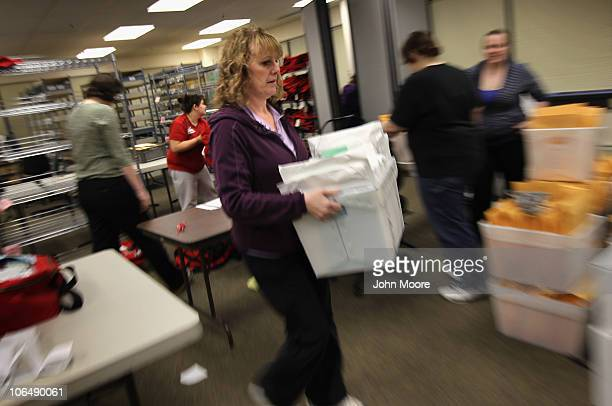 Election worker Dawn Bowie carries a boxfull of completed provisional ballots at the Alaska state elections office on November 3 2010 in Anchorage...