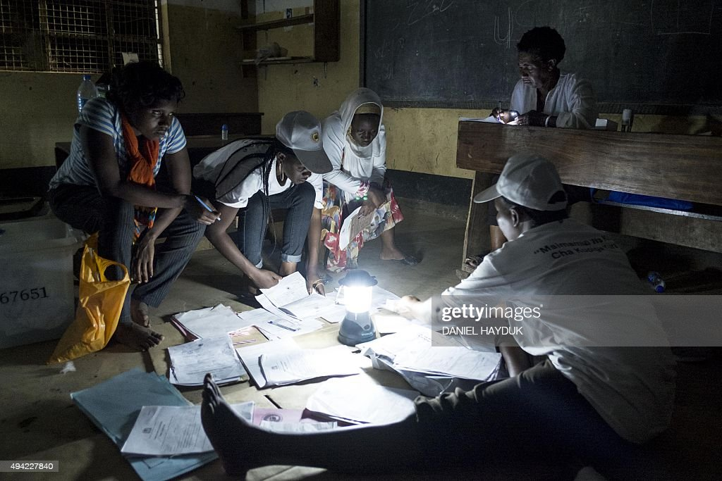 Election workers prepare to count ballots after presidential and general elections using an electric lamp to light the space at a polling station in...