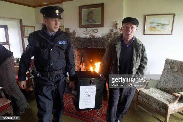Electoral officer Hugh O'Donnell with Garda Brendan McCann carry the ballot box to another cottage for the Lisbon Treaty voting on Inishfree Island...
