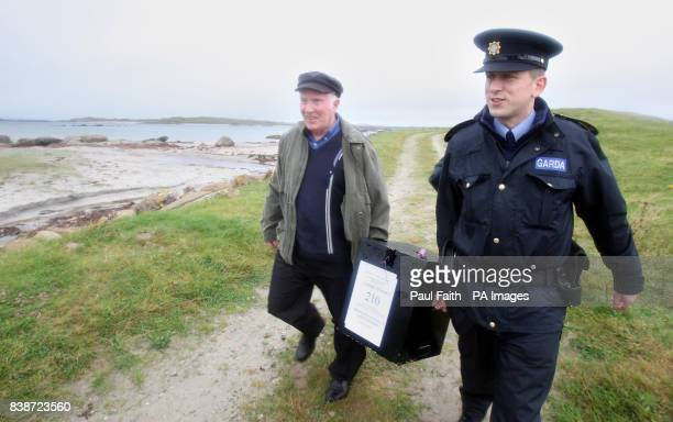 Electoral officer Hugh O'Donnell with Garda Brendan McCann carry the ballot box for the Lisbon Treaty voting on Inishfree Island off the coast of Co...