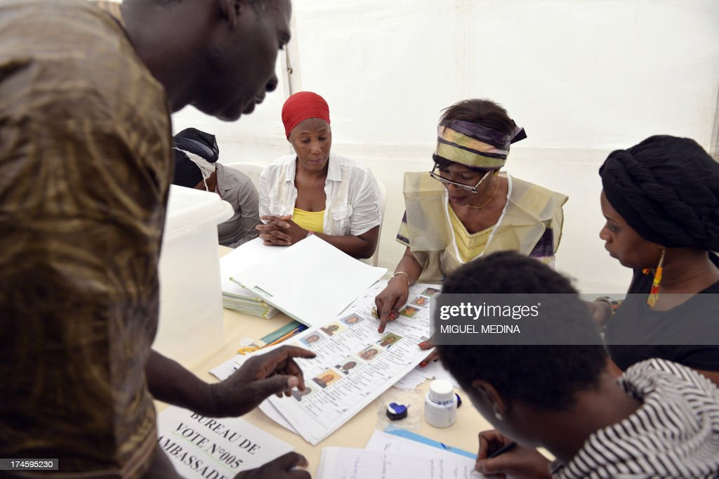 Electoral officials identify a man on a biometric voters list as he prepares to cast his vote at the Malian embassy in Paris on July 28, 2013 during the Malian presidential elections. Malians voted today for a president expected to usher in a new dawn of peace and stability in the conflict-scarred nation. They have a choice of 27 candidates as they vote for the first time since last year's military coup upended one of the region's most stable democracies, as Islamist militants hijacked a separatist uprising to seize much of the country.