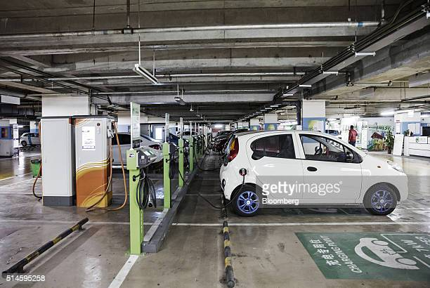 Electric automobiles sit connected to a charging station operated by Tellus Power Inc at an underground parking lot in Beijing China on Wednesday...