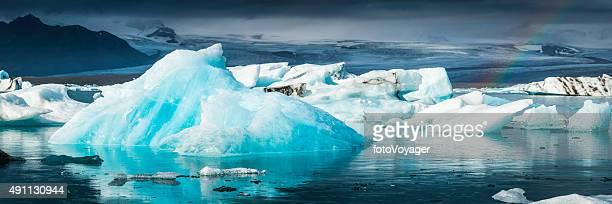 Electric blue iceberg in Arctic glacier lake panorama Jokulsarlon Iceland