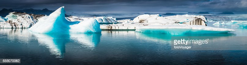 Electric blue icebergs floating in Arctic Ocean lagoon panorama Iceland