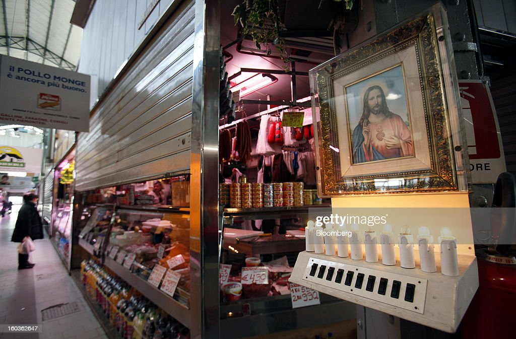 Electric candles burn beneath an image of Christ at an indoor market in Turin, Italy, on Tuesday, Jan. 29, 2013. Italy sold 8.5 billion euros ($11.4 billion) of six-month Treasury bills as rates dropped to the lowest in almost three years as the European Central Bank's pledge to buy bonds continues to provide an effective backstop even amid rising political concerns. Photographer: Alessia Pierdomenico/Bloomberg via Getty Images