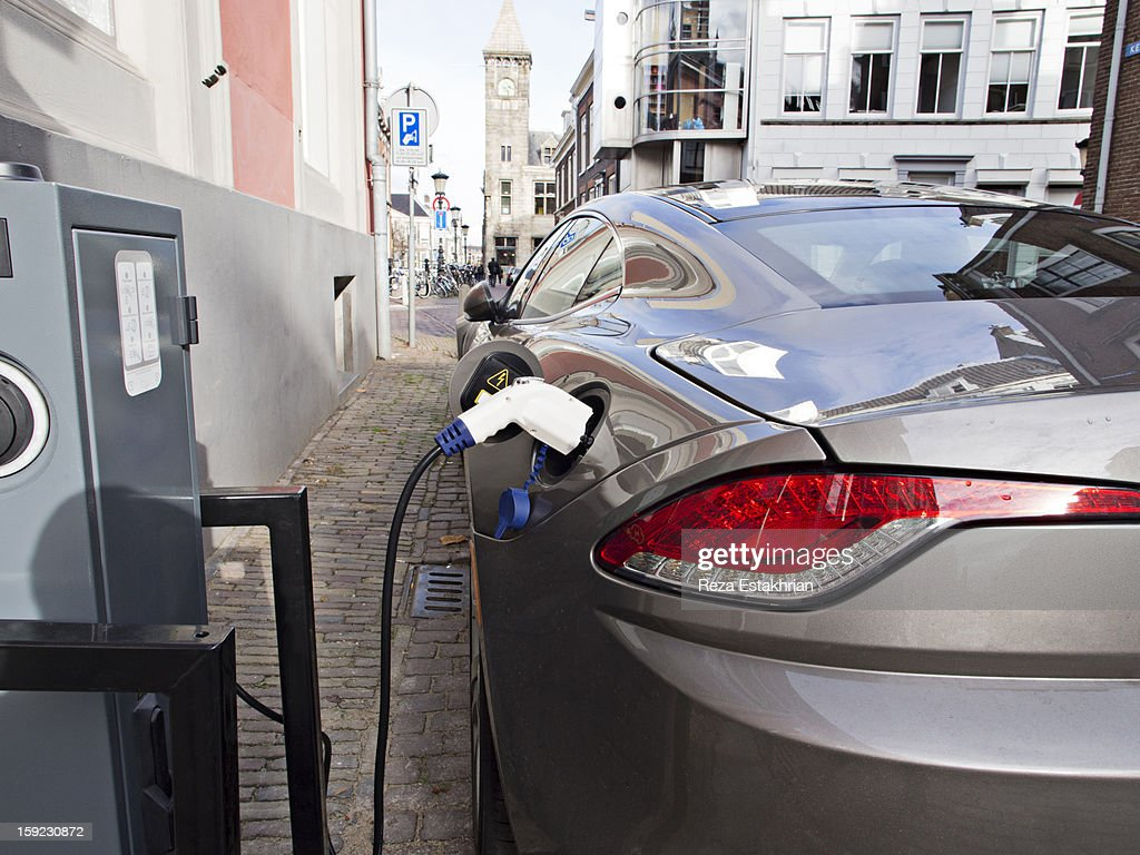 Electric car at recharging station : Stock Photo