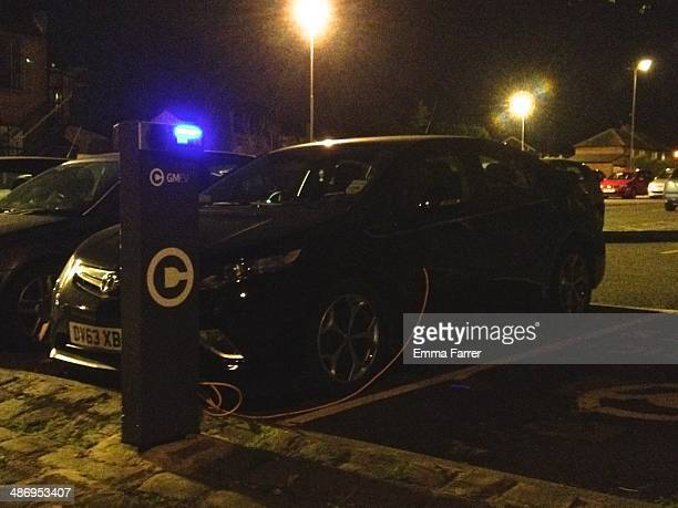Electric car being charged in a council run public car park in England during the evening