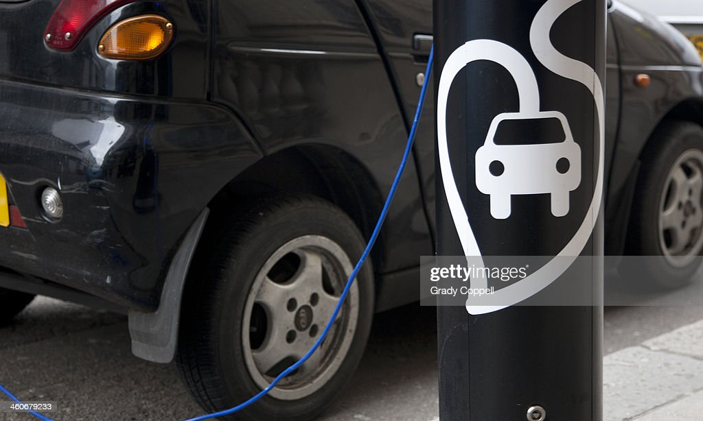 Electric car charging at street charger : Stock Photo