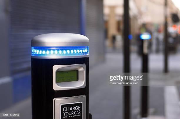 Borne de recharge pour véhicules électriques dans la rue, flou d'arrière-plan