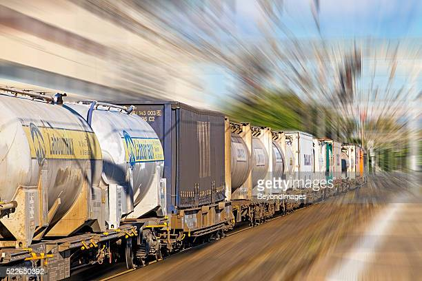 Electric cargo train passes through railway station at speed