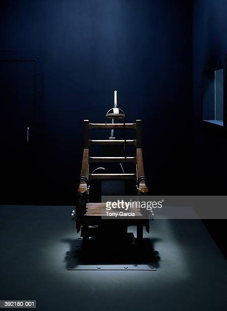 Electric chair in dark empty room,  light streaming from above