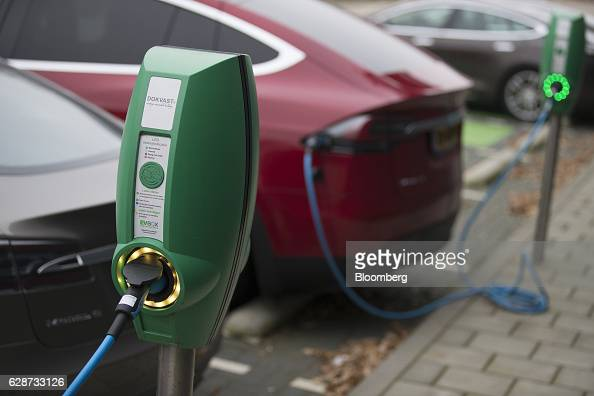 Electric charging stations sit connected to Tesla automobiles outside the Tesla Motors Inc factory in Tilburg Netherlands on Friday Dec 9 2016 A boom...
