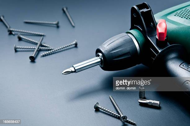 Electric drill with screws and screwdrivers on dark background