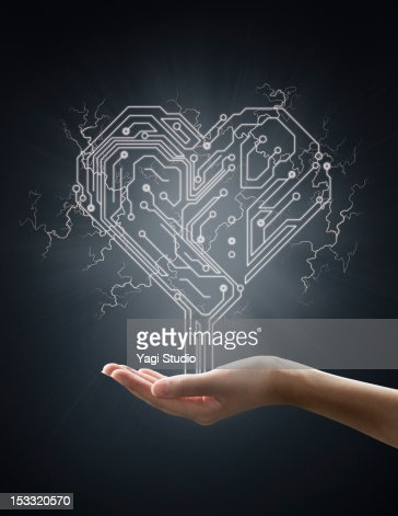 Electric energy sparks from a hand ,form of heart : Stock Photo