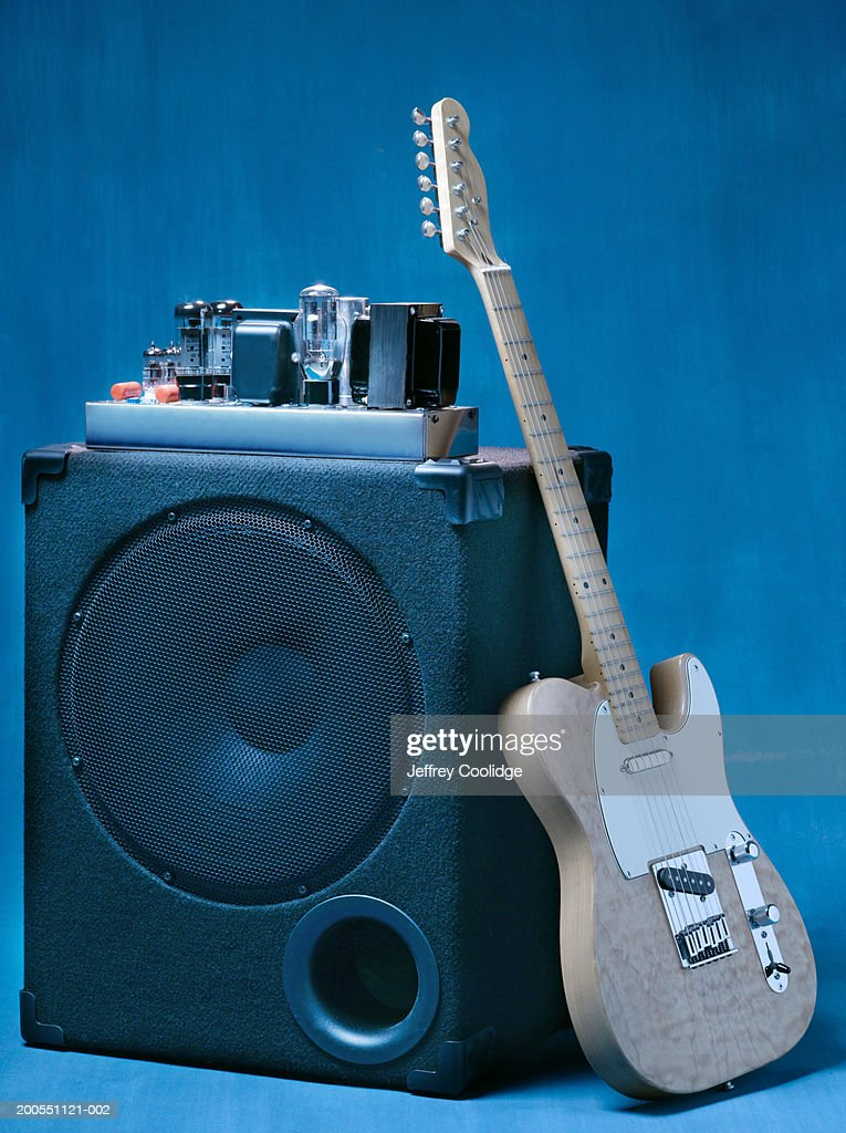Electric guitar leaning on tube amplifier. : Stock Photo