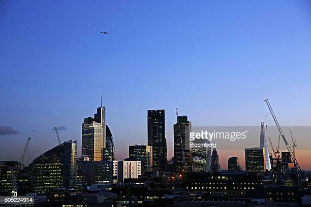 Electric lighting illuminates windows inside skyscrapers including from left the Heron Tower 30 St Mary Axe also known as 'the Gherkin' the...