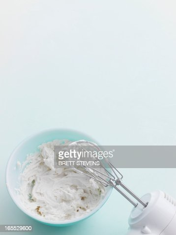 Electric mixer in bowl of frosting