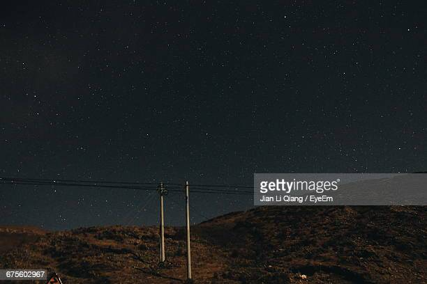 Electric Pole On Mountains Against Sky